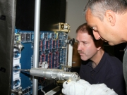 Astronauts Mike Massimino and John Grunsfeld practice procedures for repairing complex spatial NASA instruments